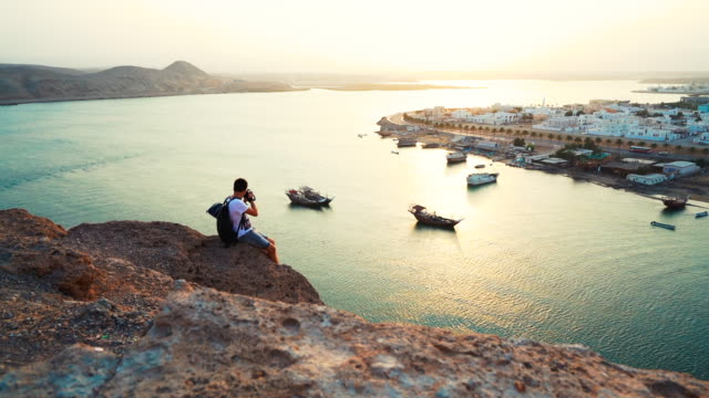 vídeos y material grabado en eventos de stock de photographer sits on rocky viewpoint photographing port - omán