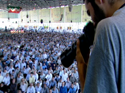 photographer snapping pictures and large gathering of worshipers for midday prayer / qom, iran - credente video stock e b–roll