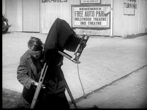 1931 B/W MONTAGE Photographer struggling to set up camera to take picture of gangster being arrested on city street/ Los Angeles, California, USA/ AUDIO