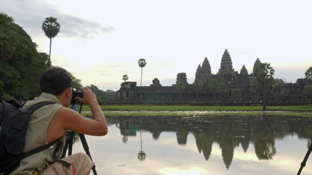 Photographer takes photographs in front of Angkor Wat Temple