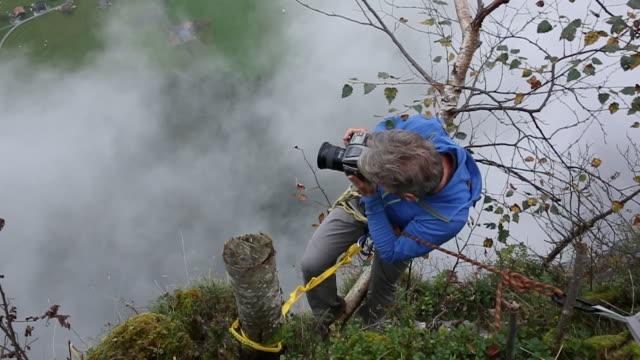stockvideo's en b-roll-footage met fotograaf neemt pic het hangen van klip rand, bergen - houten paal
