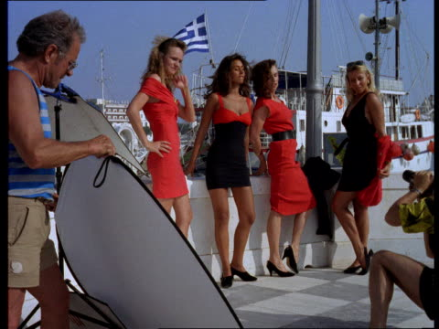 A photographer takes pictures of sexy women wearing red and black dresses near a boat dock in Greece.