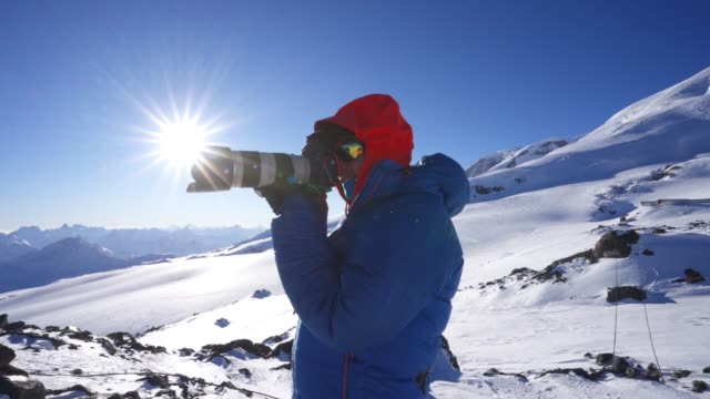 a photographer taking a picture in the cold mountains - photographer stock videos & royalty-free footage