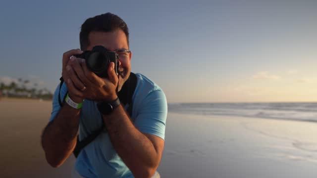 vídeos de stock, filmes e b-roll de fotógrafo tirando foto na praia ao nascer do sol - turismo urbano