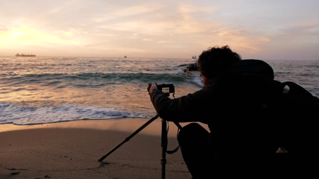 A photographer taking pictures of a beautiful seascape with unique colors on the horizon, waves in the sea water and on the beach, golden hour light, twilight, sunrise-dawn, tourism, travel destinations, epic sunset, vacations.