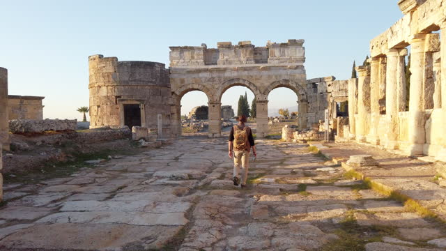 photographer tourist is walking to the frontinus gate in ancient ruins in hierapolis , pamukkale - temple building stock videos & royalty-free footage