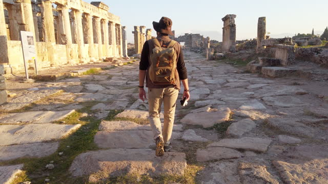 photographer tourist is walking to the frontinus gate in ancient ruins in hierapolis , pamukkale - column stock videos & royalty-free footage