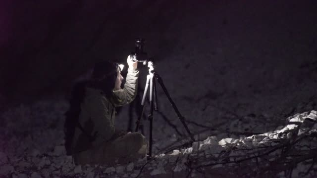 fotograf nutzt scheinwerfer nachts kameraeinstellungen anpassen - taschenlampe stock-videos und b-roll-filmmaterial
