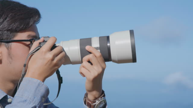 photographer using mirrorless camera with telephoto lens to taking a picture - telephoto lens stock videos and b-roll footage
