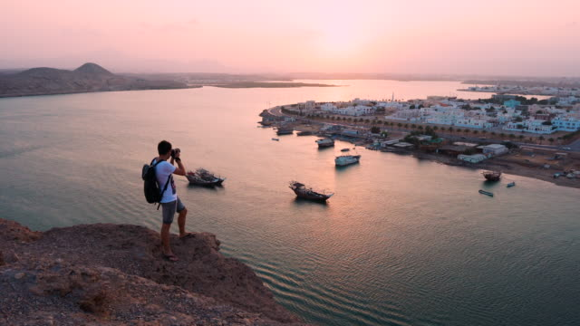 Photographer walks out to viewpoint over port to take picture