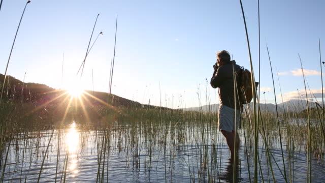 photographer walks through marsh, takes dslr pic of sunrise - 泥沼地点の映像素材/bロール