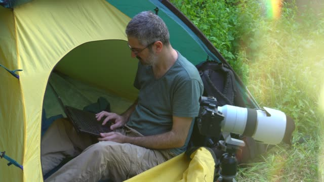 photographer working on laptop in a tent camp. - environment stock videos & royalty-free footage