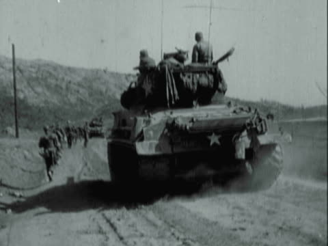 montage photographers and u.s. army soldiers taking positions behind an m4 sherman tank on a hillside road and marching during korean war / korea - armoured vehicle stock videos and b-roll footage