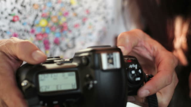 photographers looking at photos on camera - slr camera stock videos and b-roll footage