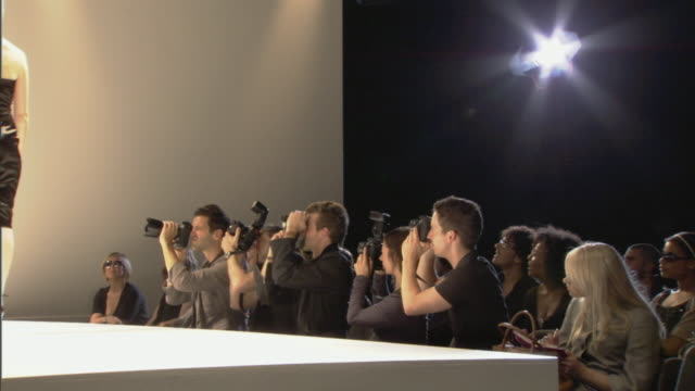 ms photographers photographing model as she walks up and down catwalk / london, england, uk - fashion show点の映像素材/bロール