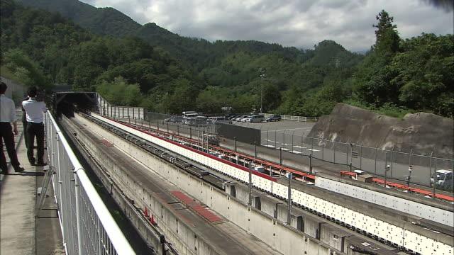 vidéos et rushes de photographers take pictures of an experimental maglev train as it speeds through tsuru city on a test run - préfecture de yamanashi