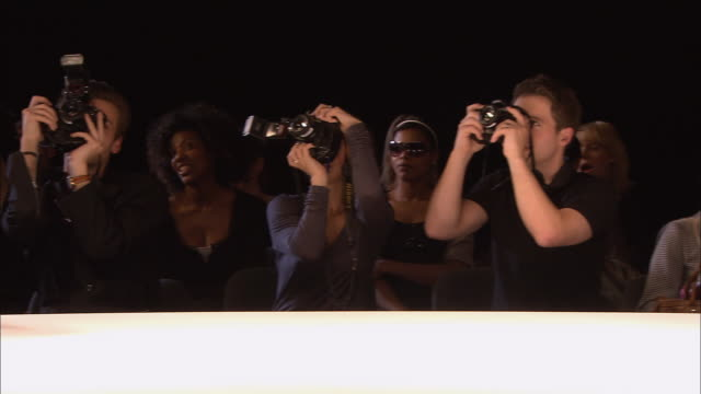 MS PAN Photographers taking pictures as model poses on catwalk at fashion show/ London, England