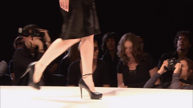 vidéos et rushes de ms pan photographers taking pictures as model poses on catwalk at fashion show/ london, england - photographe