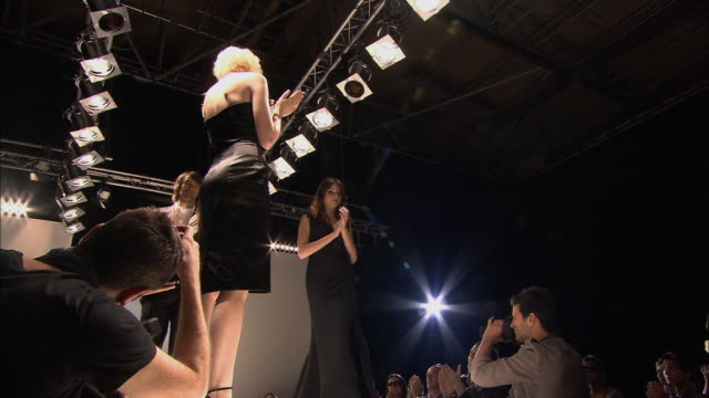 LA MS Photographers taking pictures from the end of the catwalk as models and designer walk on at end of fashion show/ MS Designer taking bow before walking off with models/ London, England