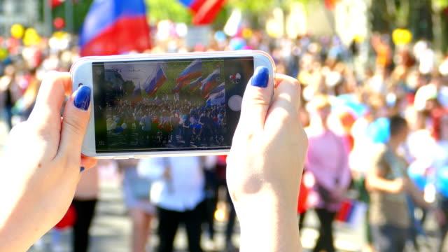 fotografieren eine festliche demonstration auf einem smartphone - demonstrant stock-videos und b-roll-filmmaterial
