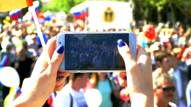 photographing a festive demonstration on a smartphone