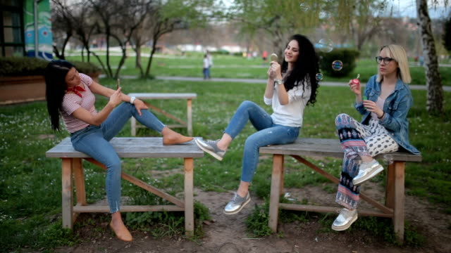 photographing friends at the park having fun - three people stock videos & royalty-free footage