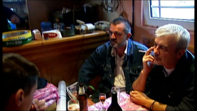 photographs of karadzic and ratko mladic in bar tilt down to local men at table barmaid, darka, speaking to reporter - ratko mladic stock videos & royalty-free footage