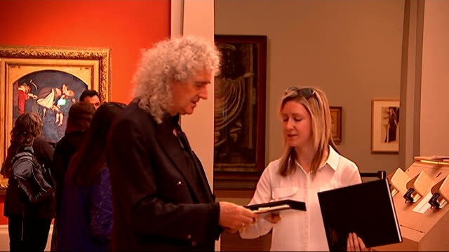 brian may lends rare stereograph photographs to tate britain; england: london: tate britain: int visitors looking at photographs and painting s... - curator stock videos & royalty-free footage