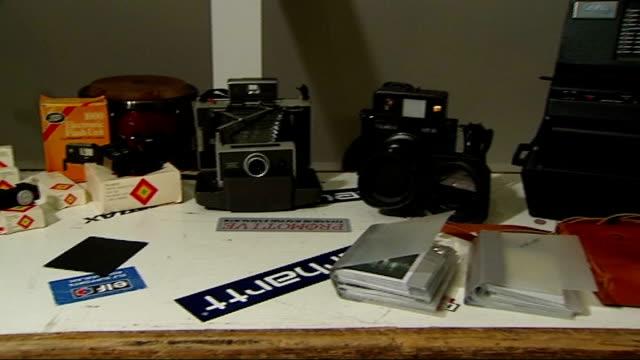 polaroid to end instant film production london int polaroid cameras and film on desk - polaroid video stock e b–roll