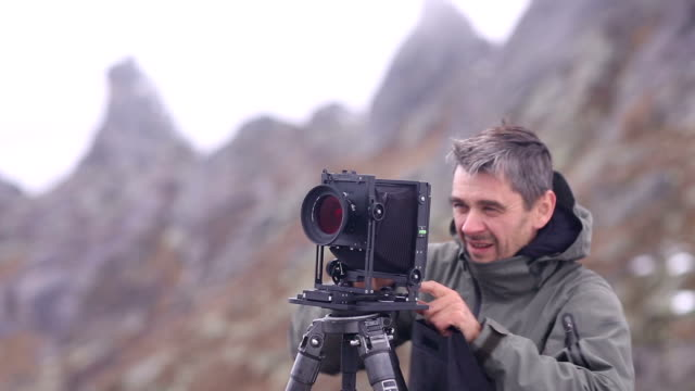 photography with the old school camera in the mountains. - one mature man only stock-videos und b-roll-filmmaterial