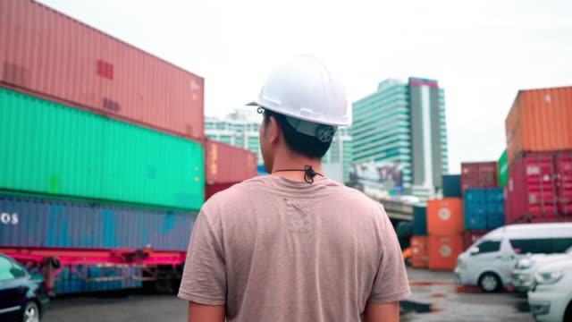 倉庫に立つ白い帽子をかぶった若者の写真 安全と輸送の概念 - 倉庫作業員点の映像素材/bロール