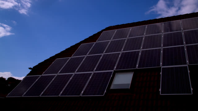 photovoltaic panels reflect clouds on a roof in saarland, germany. - dach stock-videos und b-roll-filmmaterial