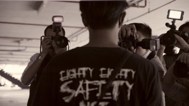 stockvideo's en b-roll-footage met phtographers surrounding man - media interview