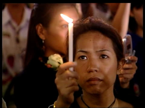 phuket thai woman holding candle and single white rose cs white rose and burning candle cms woman holding candle and single white rose mourners at... - single rose stock videos & royalty-free footage