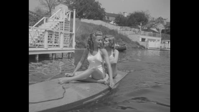 phyllis coates and patricia northrup in halter top one piece bathing suits sit on motorboard a motorized surfboard in toluca lake as it moves past... - warner bros stock videos & royalty-free footage