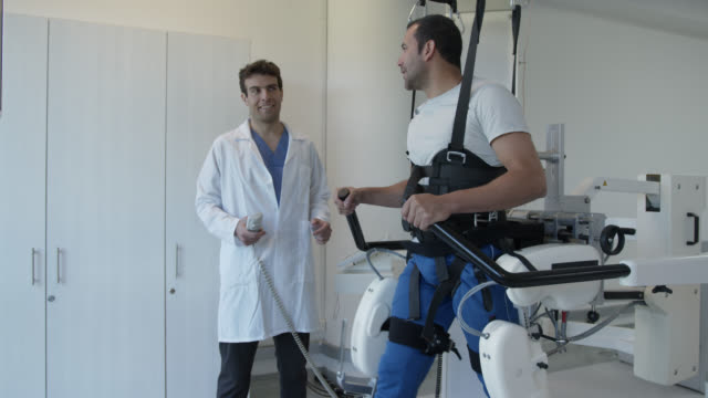 vídeos de stock e filmes b-roll de physical therapist adjusting the speed on treadmill while patient on exoskeleton robot is learning how to walk again - recuperação