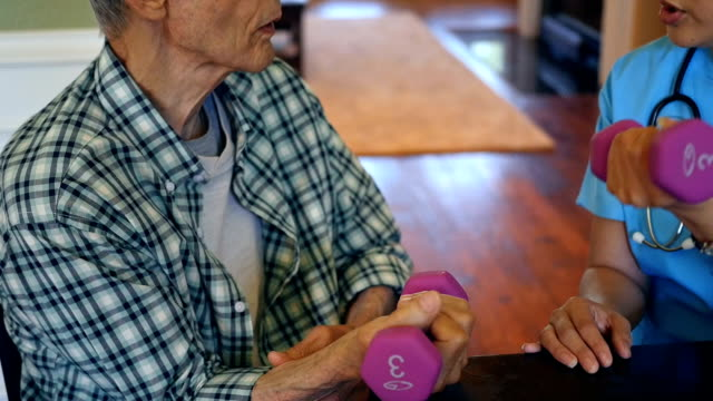 Physical therapist assists senior male patient during home visit
