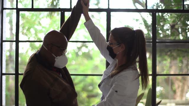 vídeos de stock, filmes e b-roll de fisioterapeuta fazendo exercícios com paciente sênior em casa - usando máscara facial - moving image