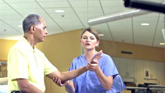 vídeos de stock, filmes e b-roll de fisioterapeuta, examinando o pulso do paciente - fisioterapeuta