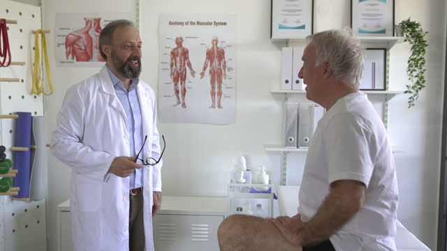 physical therapist having a conversation with patient about his injury recovery - greeting stock videos & royalty-free footage
