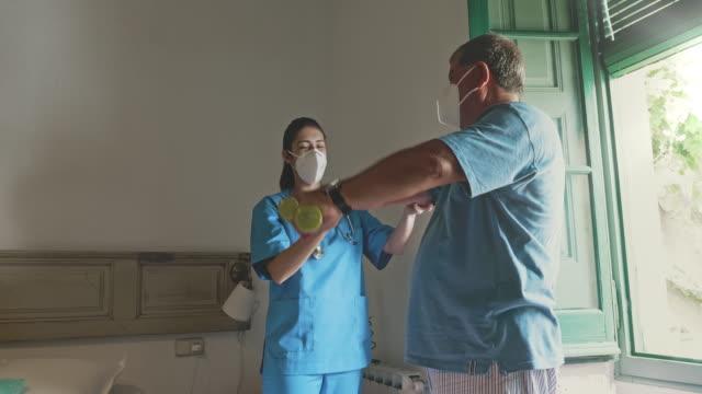 vídeos y material grabado en eventos de stock de fisioterapeuta ayudando a los hombres mayores a mejorar la movilidad durante la pandemia - fisioterapia deportiva