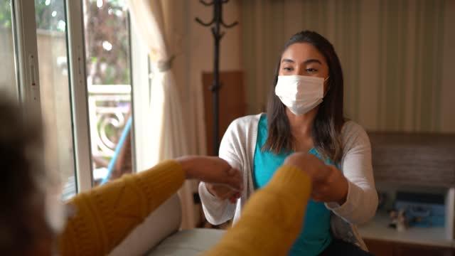 vídeos de stock, filmes e b-roll de fisioterapeuta ajudando idosa fazendo exercício em casa - usando máscara facial protetora - braço humano