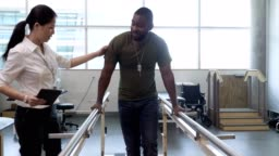 Physical therapist helps military patient on parallel bars