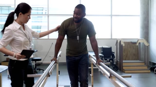 vídeos de stock e filmes b-roll de physical therapist helps military patient on parallel bars - soldado exército