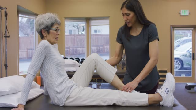 physical therapist massaging senior female's calf muscle - physical therapy stock videos & royalty-free footage