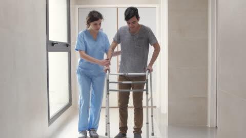stockvideo's en b-roll-footage met fysiotherapeut motiveren haar patiënt terwijl hij met moeite met behulp van een wandelaar via de hal van het ziekenhuis was - tegenspoed