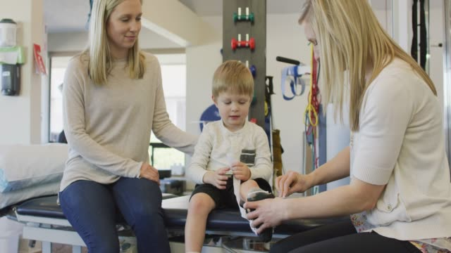 vídeos y material grabado en eventos de stock de fisioterapeuta colocando suave fundido en niño - fisioterapia deportiva