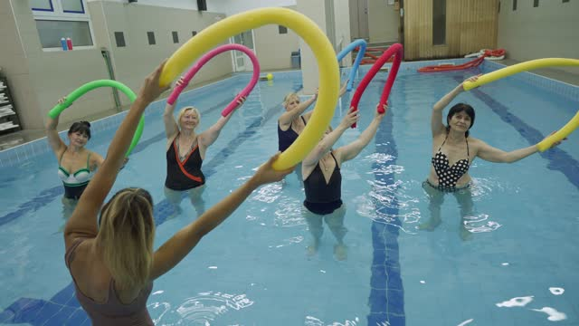physical therapist showing a stretching exercise during hydrotherapy, while her senior clients using a noodle floats for better balance - hydrotherapy stock videos & royalty-free footage