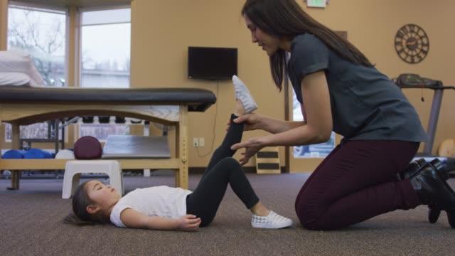 vídeos y material grabado en eventos de stock de fisioterapeuta, estirando la pierna de una joven - fisioterapia deportiva