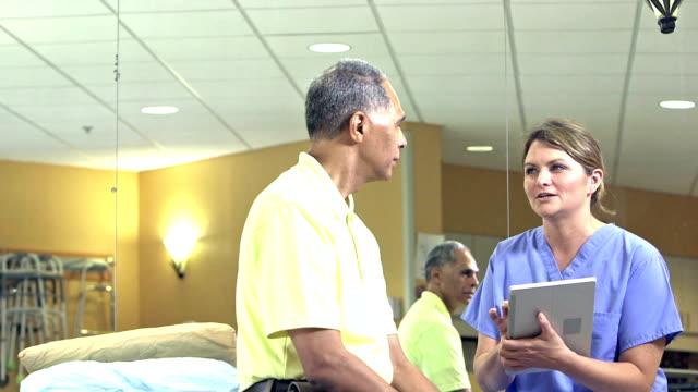 vídeos de stock, filmes e b-roll de fisioterapeuta com tablet digital fala com paciente - fisioterapeuta